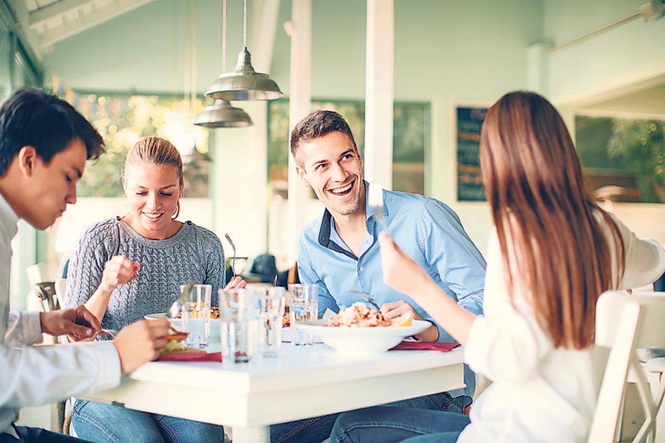Eine Gruppe Freunde sitzt an einem Tisch. Thema: CED