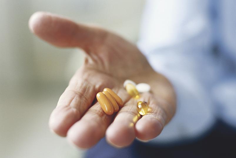 Chronische Verstopfung? Ein Mann bietet Pillen in seiner Hand an.