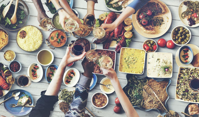 Tisch mit vielen verschiedenen Speisen; Menschen, die mit Weingläsern anstoßen.