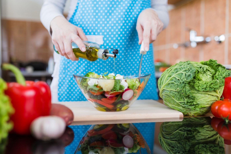 Person bereitet einen bunten Salat vor.