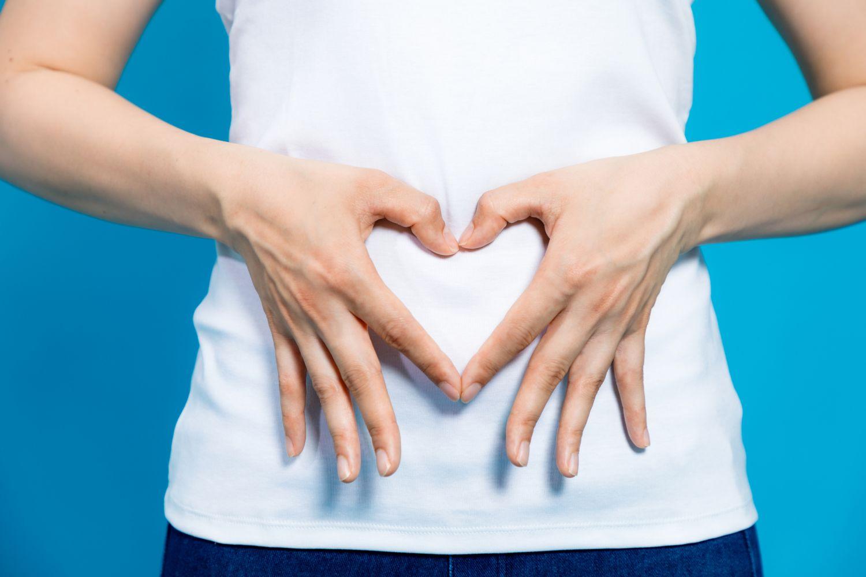 Frau formt mit den Händen ein Herz über ihrem Bauch. Thema: Verdauungssystem