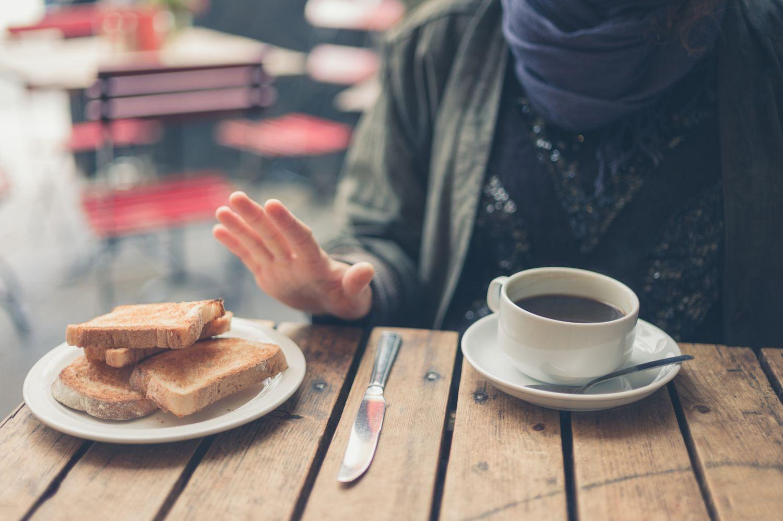 Ein Mann lehnt Weizentoast ab. Thema: Nahrungsmittelunverträglichkeit