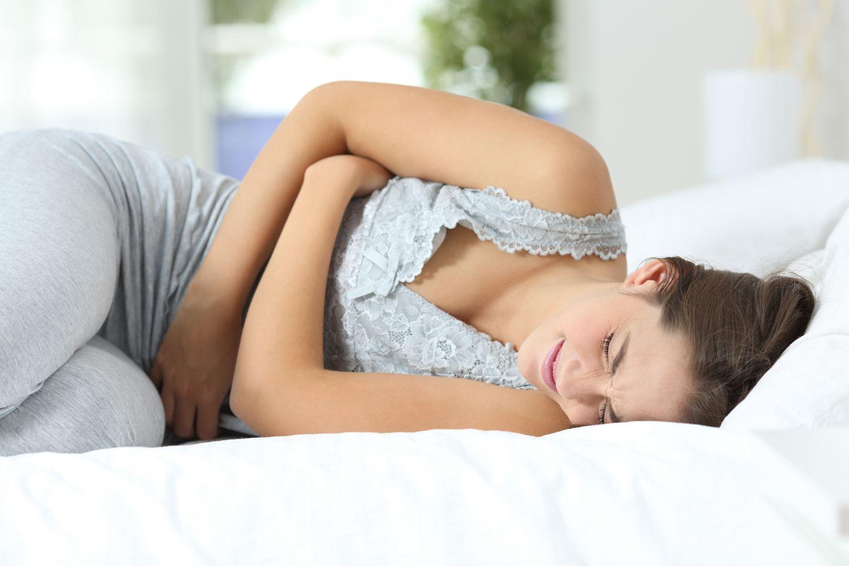 Frau liegt zusammengekrümmt wegen Bauchschmerzen bei Magenschleimhautentzündung.