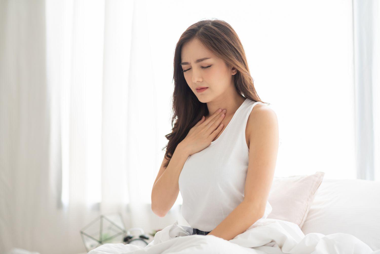 Frau hält sich die Brust. Thema: Sodbrennen