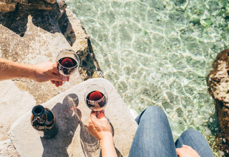 Zwei Menschen stoßen mit Rotweingläsern an. Thema: Krebsvorsorge