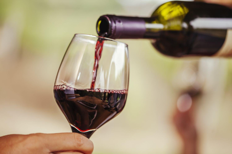Weinglas wird mit Rotwein gefüllt. Thema: Sodbrennen und Protonenpumpenhemmer