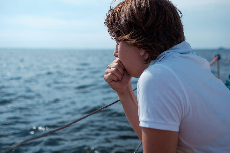 Ein Junge beugt sich über die Reling eines Schiffes. Sodbrennen kann lästig sein.